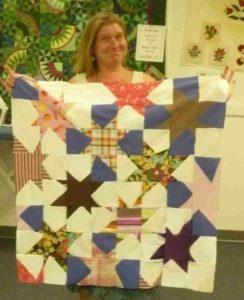 """La créatrice avec un patchwork artisanale """"twinkling stars"""", réalisé lors d'un stage de patchwork aux Etats-Unis"""